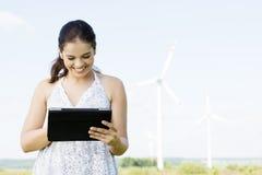 Muchacha adolescente con la tableta al lado de la turbina de viento. Fotografía de archivo