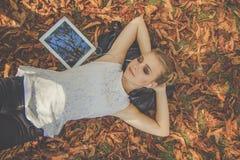 Muchacha adolescente con la tableta digital en parque del otoño Imagenes de archivo