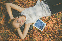 Muchacha adolescente con la tableta digital que miente en las hojas Foto de archivo libre de regalías