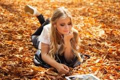 Muchacha adolescente con la tableta digital que miente en las hojas Foto de archivo