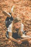 Muchacha adolescente con la tableta digital que miente en las hojas Fotografía de archivo libre de regalías