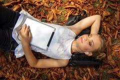 Muchacha adolescente con la tableta digital que miente en parque del otoño Fotografía de archivo