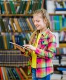 Muchacha adolescente con la tableta en una biblioteca Fotografía de archivo