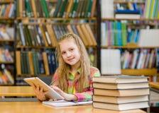 Muchacha adolescente con la tableta que trabaja en biblioteca Foto de archivo libre de regalías