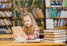 Muchacha adolescente con la tableta que trabaja en biblioteca Foto de archivo