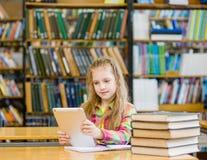 Muchacha adolescente con la tableta que trabaja en biblioteca Fotos de archivo libres de regalías
