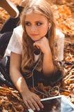 Muchacha adolescente con la tableta y los auriculares digitales Fotografía de archivo libre de regalías