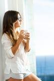 Muchacha adolescente con la taza de café en la ventana. Fotografía de archivo libre de regalías