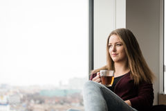 Muchacha adolescente con la taza de té que mira a través de la ventana Fotografía de archivo