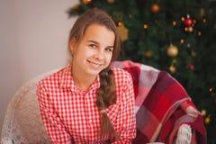 Muchacha adolescente con las coletas en una camisa de tela escocesa roja Foto de archivo