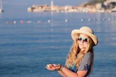 Muchacha adolescente con las estrellas de mar que se colocan en la playa Imagen de archivo libre de regalías