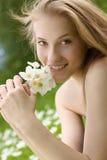 Muchacha adolescente con las flores blancas en parque Foto de archivo libre de regalías