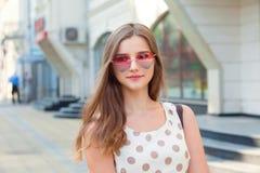 Muchacha adolescente con las gafas de sol en forma de corazón del sombrero moreno largo del rosa que miran lejos sonrientes fotografía de archivo libre de regalías