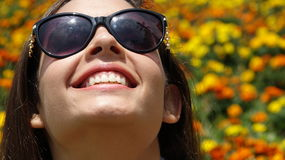 Muchacha adolescente con las gafas de sol y las flores Fotografía de archivo