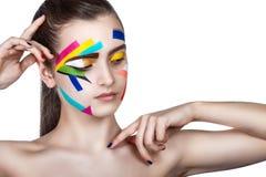 Muchacha adolescente con las rayas coloreadas en la cara Arte brillante del maquillaje foto de archivo libre de regalías