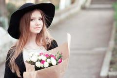 Muchacha adolescente con las rosas al aire libre Fotos de archivo