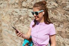 Muchacha adolescente con longboard, smartphone y los auriculares Fotografía de archivo