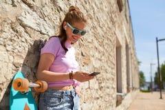 Muchacha adolescente con longboard, smartphone y los auriculares Fotos de archivo libres de regalías