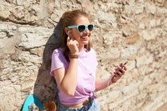 Muchacha adolescente con longboard, smartphone y los auriculares Fotos de archivo