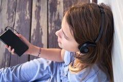 Muchacha adolescente con los auriculares que disfruta de música de un smartphone al aire libre Fotos de archivo libres de regalías
