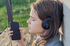 Muchacha adolescente con los auriculares que disfruta de música de un smartphone al aire libre Fotografía de archivo