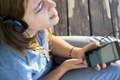 Muchacha adolescente con los auriculares que disfruta de música de un smartphone al aire libre Imágenes de archivo libres de regalías