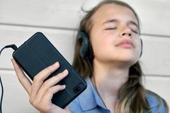 Muchacha adolescente con los auriculares que escucha y que disfruta de música de un smartphone Fotos de archivo