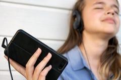 Muchacha adolescente con los auriculares que escucha y que disfruta de música de un smartphone Foto de archivo libre de regalías
