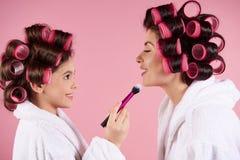 Muchacha adolescente con los bigudíes que hacen maquillaje a la mamá Imágenes de archivo libres de regalías