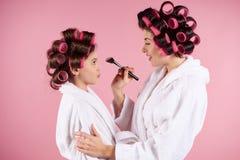 Muchacha adolescente con los bigudíes que hacen maquillaje a la mamá Imagen de archivo