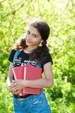 Muchacha adolescente con los libros en la naturaleza Imagenes de archivo