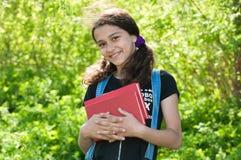 Muchacha adolescente con los libros en la naturaleza Imagen de archivo