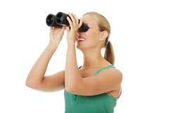 Muchacha adolescente con los prismáticos. Fotografía de archivo