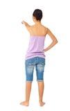 Muchacha adolescente con los tejanos y el top sin mangas mientras que señala con su f Fotografía de archivo