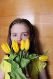 Muchacha adolescente con los tulipanes amarillos Foto del retrato en el fondo de madera Foto de archivo libre de regalías