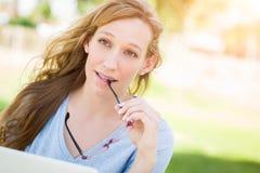 Muchacha adolescente con los vidrios al aire libre usando su ordenador portátil Fotos de archivo libres de regalías