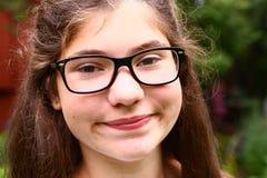 Muchacha adolescente con los vidrios de vista corta y grueso marrón Fotografía de archivo libre de regalías