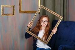 Muchacha adolescente con los vidrios que llevan a cabo un marco vacío Imagen de archivo