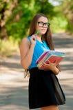 Muchacha adolescente con los vidrios y los libros en manos Imagenes de archivo