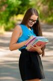 Muchacha adolescente con los vidrios y los libros en manos Foto de archivo libre de regalías