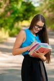Muchacha adolescente con los vidrios y los libros en manos Fotografía de archivo