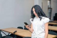 Muchacha, adolescente con smartphone en sala de clase, durante la lección Fotografía de archivo libre de regalías