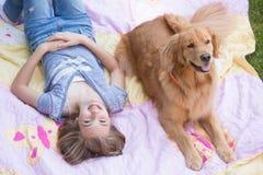 Muchacha adolescente con su perro del golden retriever Imagenes de archivo
