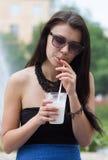 Muchacha adolescente con un batido de leche el día de verano Imagen de archivo libre de regalías