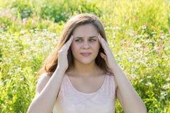 Muchacha adolescente con un dolor de cabeza en un prado floreciente Foto de archivo libre de regalías