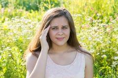 Muchacha adolescente con un dolor de cabeza en un prado floreciente Fotos de archivo