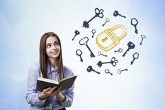 Muchacha adolescente con un libro, un candado y llaves Fotografía de archivo