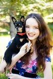 Muchacha adolescente con un pequeño perro Fotografía de archivo