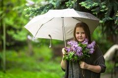 Muchacha adolescente con un ramo de lilas, colocándose debajo de un paraguas Foto de archivo