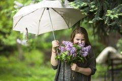 Muchacha adolescente con un ramo de lilas, colocándose debajo de un paraguas Imágenes de archivo libres de regalías
